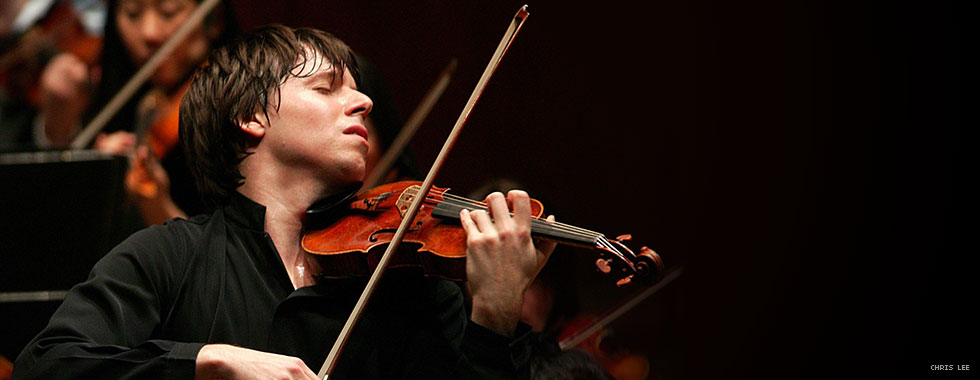 A musician playing a violin closes his eyes and throws his head back to the left.