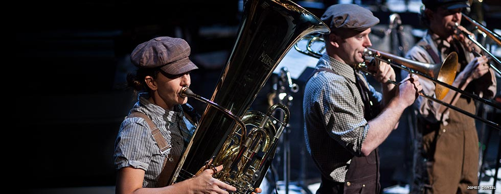 Clad in early 20th-century-inspired clothing and hats, jazz musicians from Darcy James Argue's Secret Society play their tuba and trombones.