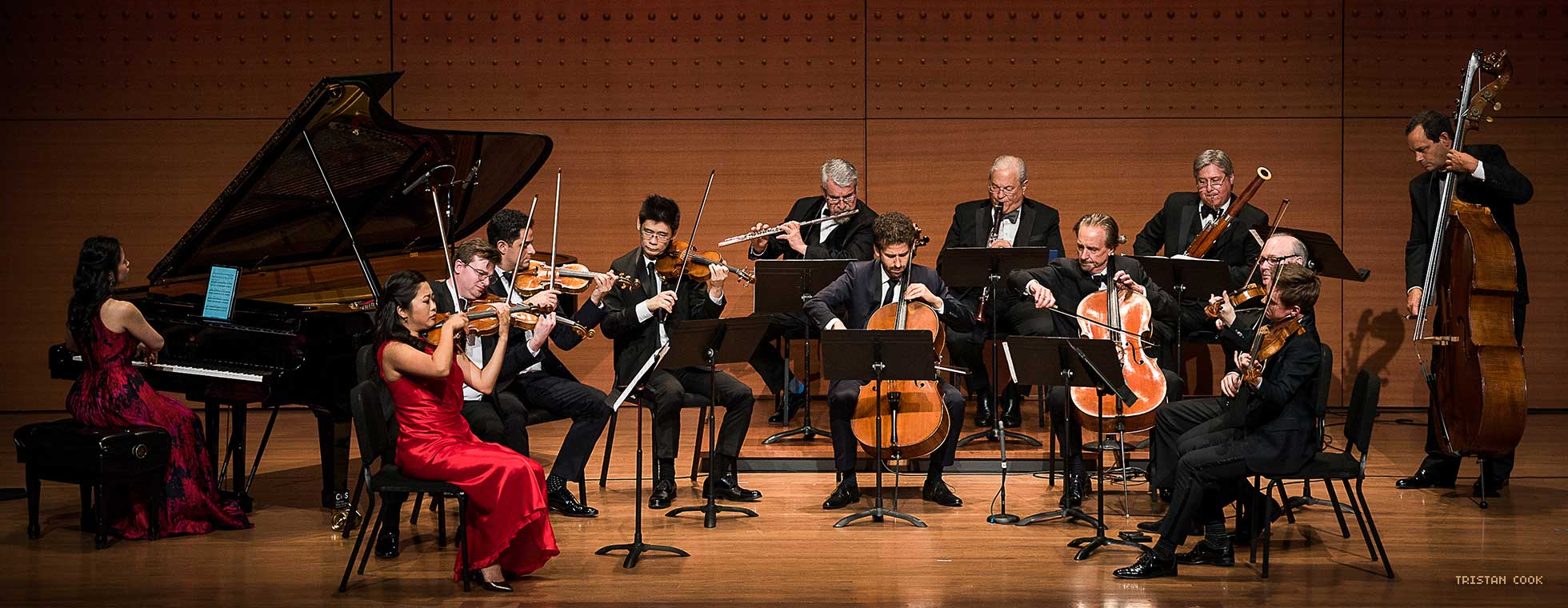 Thirteen musicians in formal clothing perform on stage.