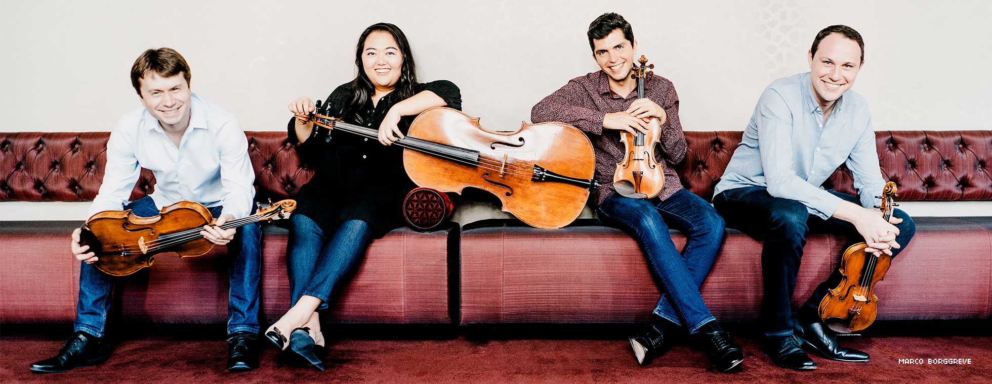 Members of the quartet sit on plush couches with their instruments.