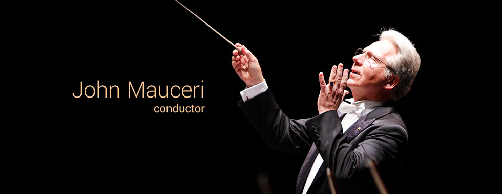 An orchestra conductor looks upward as he points a baton in his right hand and straightens the fingers on his left hand.