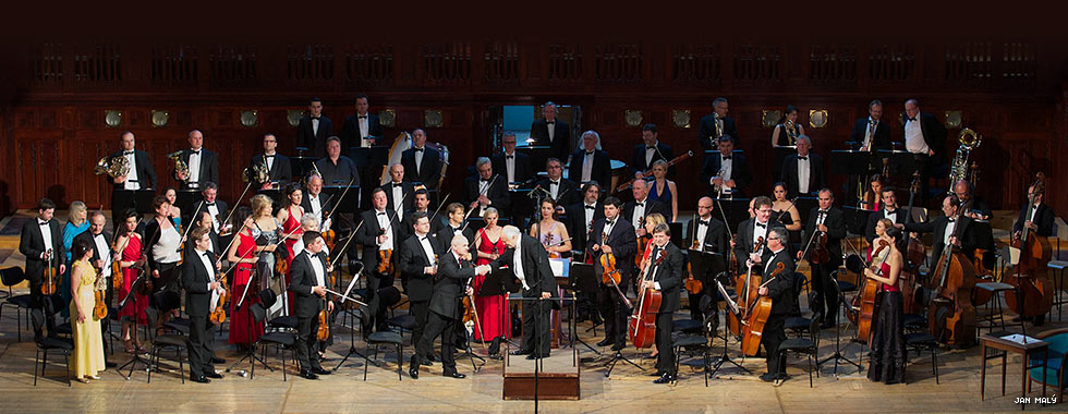 A conductor standing in front of a group of musicians holding their instruments shakes the hand of one of the orchestra members.