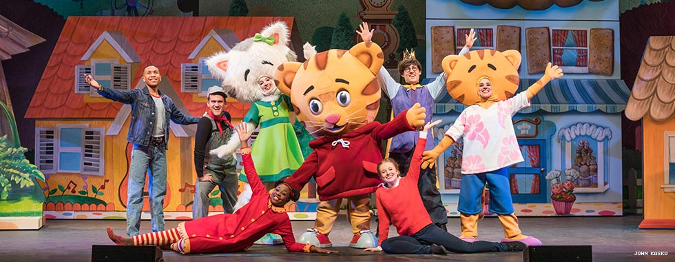 "Actors dressed as characters from the PBS kids' show ""Daniel Tiger's Neighborhood"" strike a pose with their hands up and outstretched in front of a set depicting cartoon-like houses."