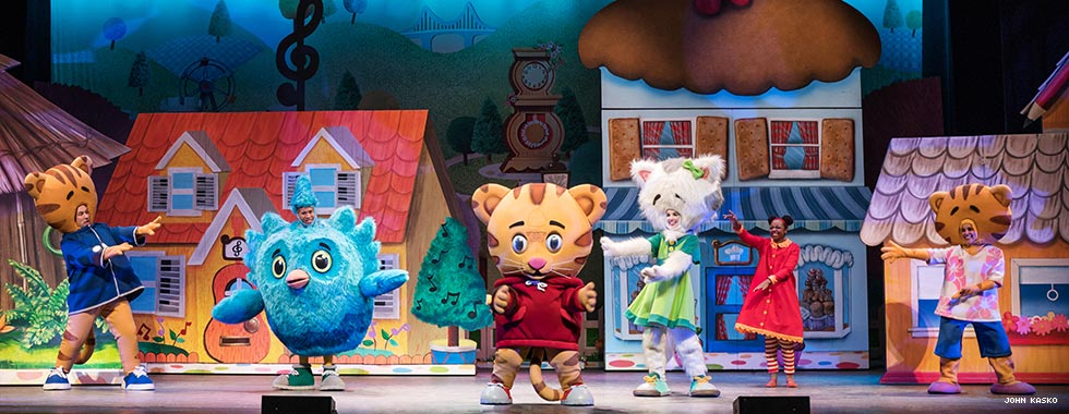 "Actors dressed as characters from the PBS kids' show ""Daniel Tiger's Neighborhood"" dance and make gestures in front of a set depicting cartoon-like houses."