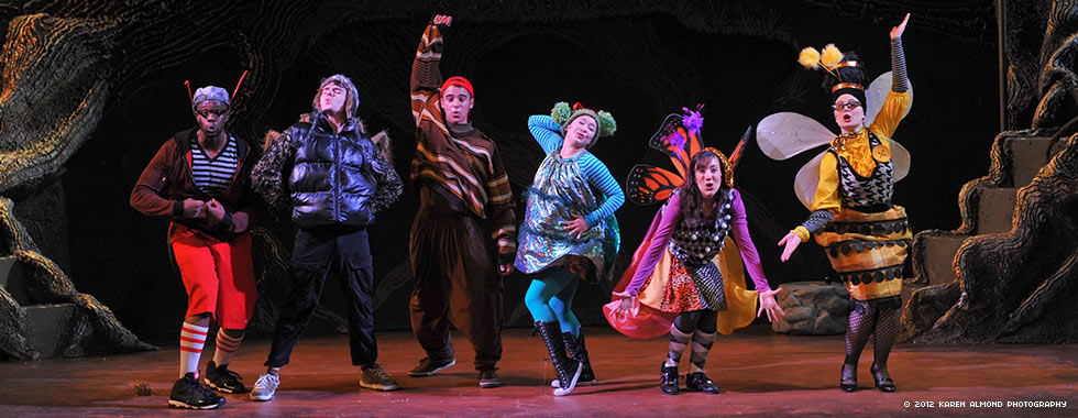 Six actors strike poses and make hand gestures while dressed in stylized insect costumes.