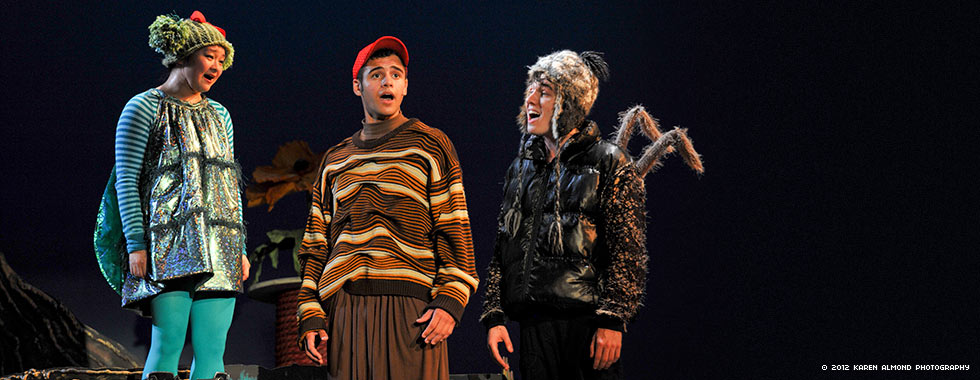 Actors dressed in costumes depicting a fly, a worm, and a spider sing in unison.