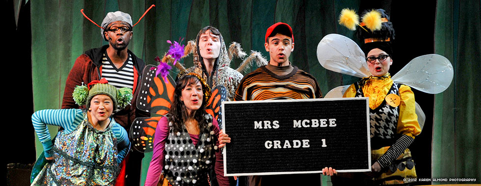 Actors dressed in costumes depicting a fly, beetle, butterfly, spider, worm, and bee hold a sign announcing Mrs. McBee's first-grade class.