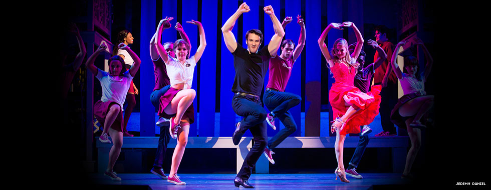 Dancers each hold up both arms above their head and bend a knee to lift up their right foot in an on-stage dance routine.