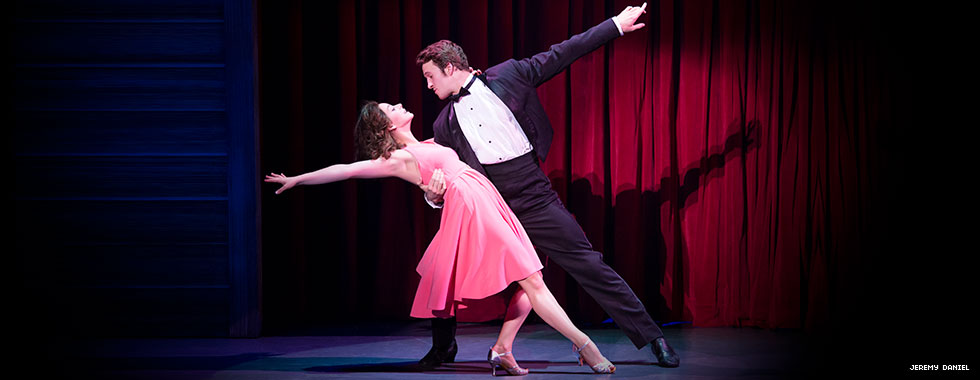 A tuxedo-clad male dancer dips his dancing partner with his right arm around her waist and extends his left arm straight back as she bends a knee and leans back with her right arm extended straight.