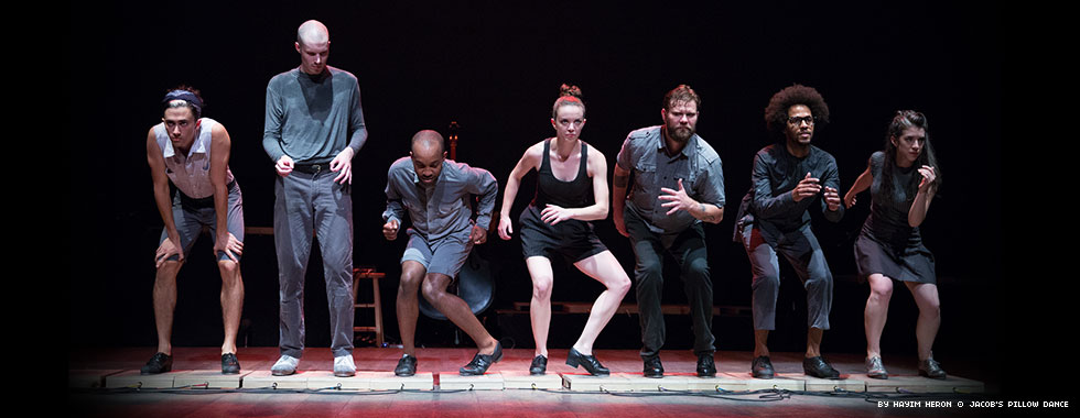 Seven dancers bend their knees and elbows in preparation of a tap-dance move.