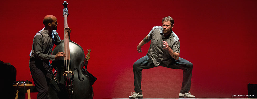 A dancer stands bent at the knees with feet pointed outward while a cellist next to him plays his instrument.