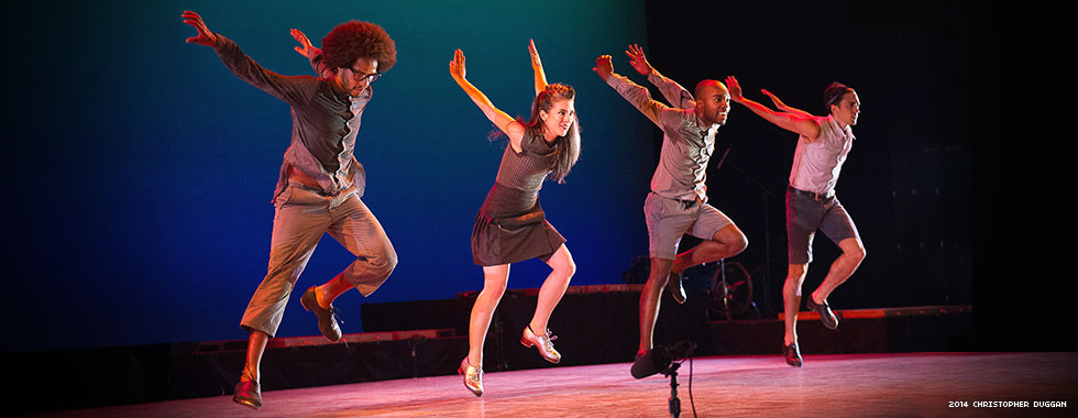 Two men and two women swing their arms straight behind them in a tap-dance move.