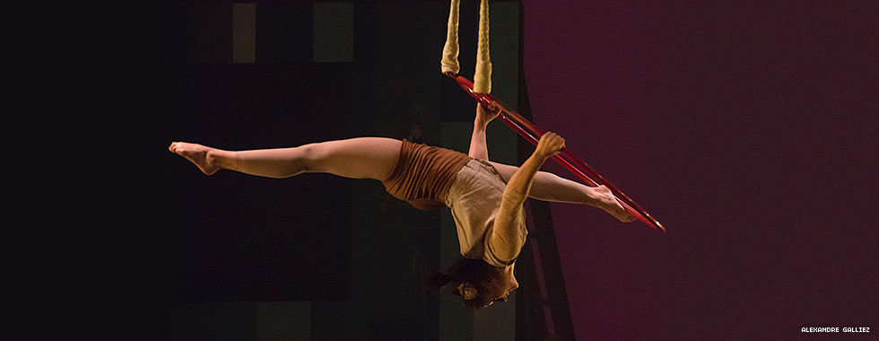 An acrobat outstretches her legs in opposite directions and bends her head and neck back while holding on to a hula hoop that's suspended from ropes.