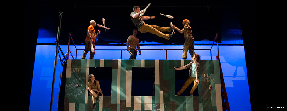 Four acrobats juggle pins atop a set resembling a building with windows while two performers sit in the openings and watch.