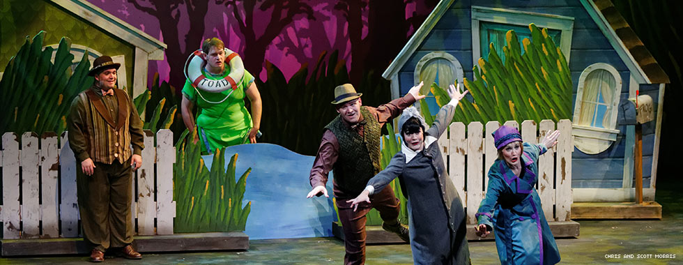 Actors portraying Frog and Toad—one wearing a vest, bow-tie, and hat, and the other with a life preserver around his neck—watch three actors performing a choreographed song-and-dance number in front of a scene that resembles houses next to a pond.