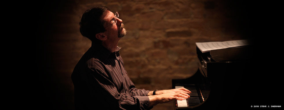 Fred Hersch closes his eyes and leans back while he plays the piano.