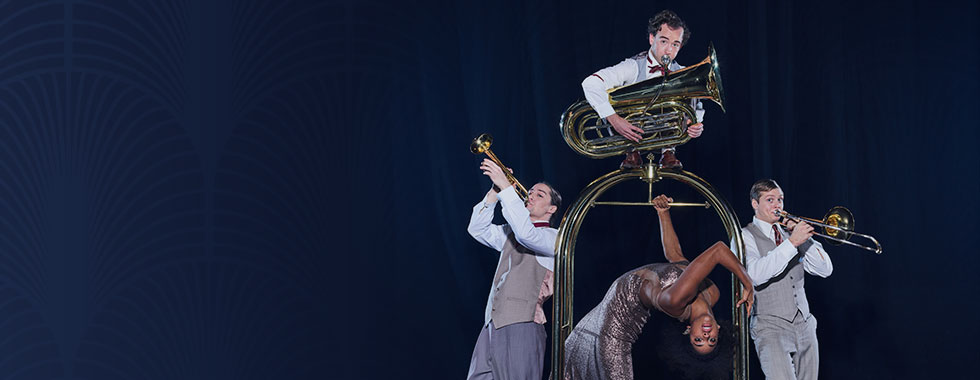Three men dressed in suit vests and ties each play a brass instrument while surrounding a female acrobat hanging from a hotel luggage rack with her head dipped back.