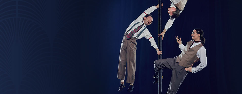 Three male acrobats use their limbs to hold on to a pole in astonishing positions.