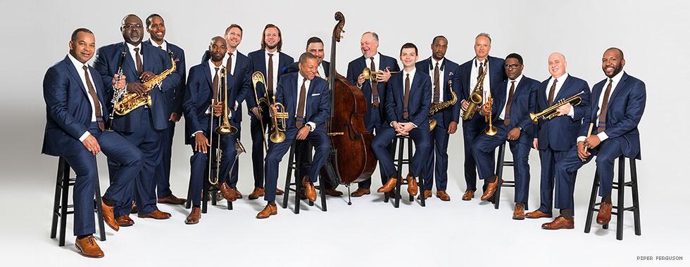The entire jazz orchestra stand around Wynton Marsalis