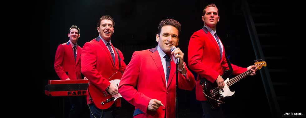 The Four Seasons, dressed in matching suit jackets, each pose with their instrument while one actor stands in the front at a microphone.