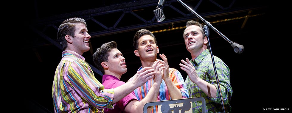 Four actors portraying the Four Seasons crowd around a microphone in a singing scene.
