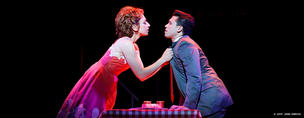 An actress leans over a dinner setting to grab an actor by the suit jacket for a kiss.