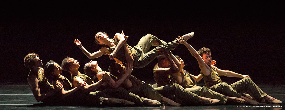 Eight dancers sit interlocked one behind the other while passing a female dancer front to back above them.