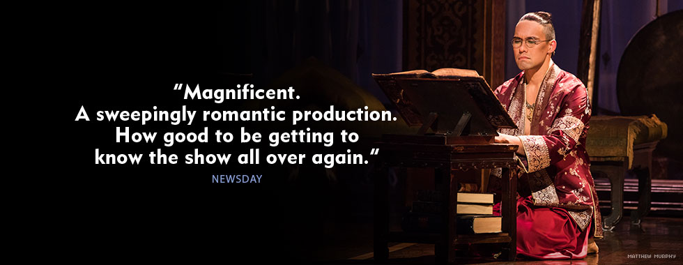 """""""Magnificent. A sweepingly romantic production. How good to be getting to know the show all over again."""" Newsday. A man dressed in traditional Thai clothing sits on his knees while he reads a large book."""
