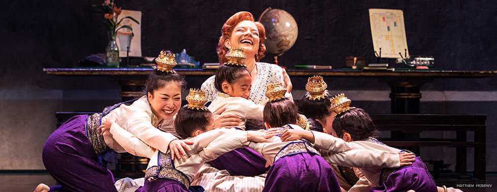 A woman laughs as a group of children and another woman encircle her for a hug.