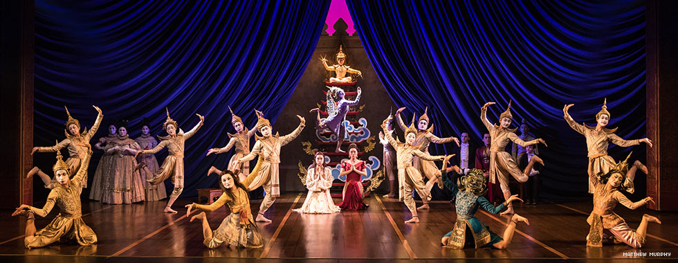 A stage scene features actors dressed to resemble Buddhist and Thai figures while two people kneel in the center of the dancers and hold their hands to their chests in prayer.