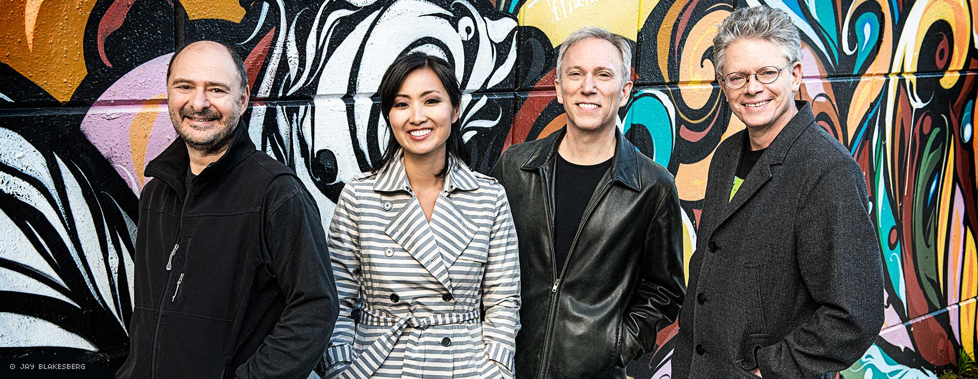 Quartet members stand in a row in front of a mural wall.