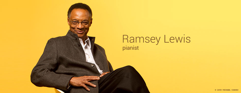 Pianist Ramsey Lewis leans back in a chair and smiles for the camera.