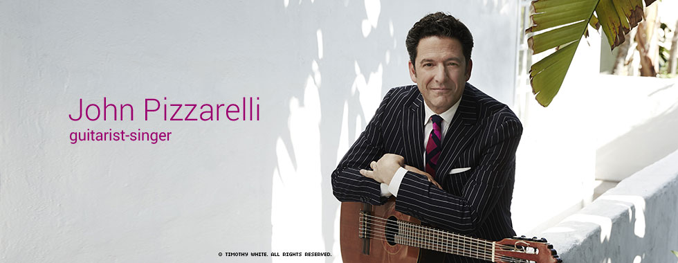 Musician and vocalist John Pizzarelli, his arms folded atop his guitar, smiles for the camera.