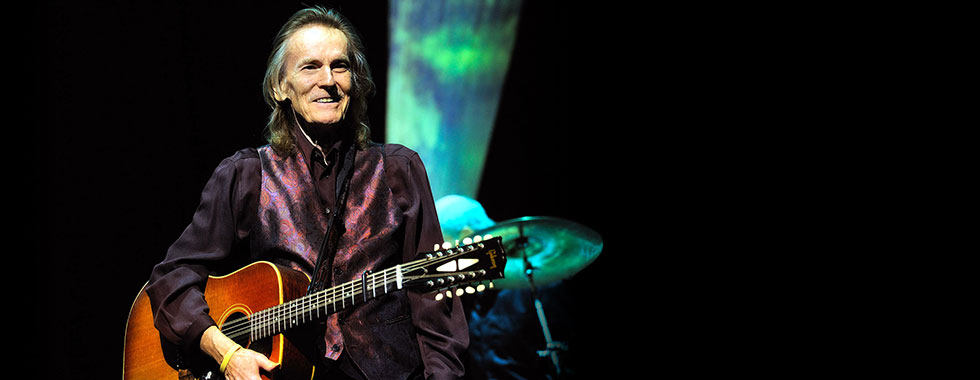 Gordon Lightfoot stands and smiles as he holds an acoustic guitar under his right arm.