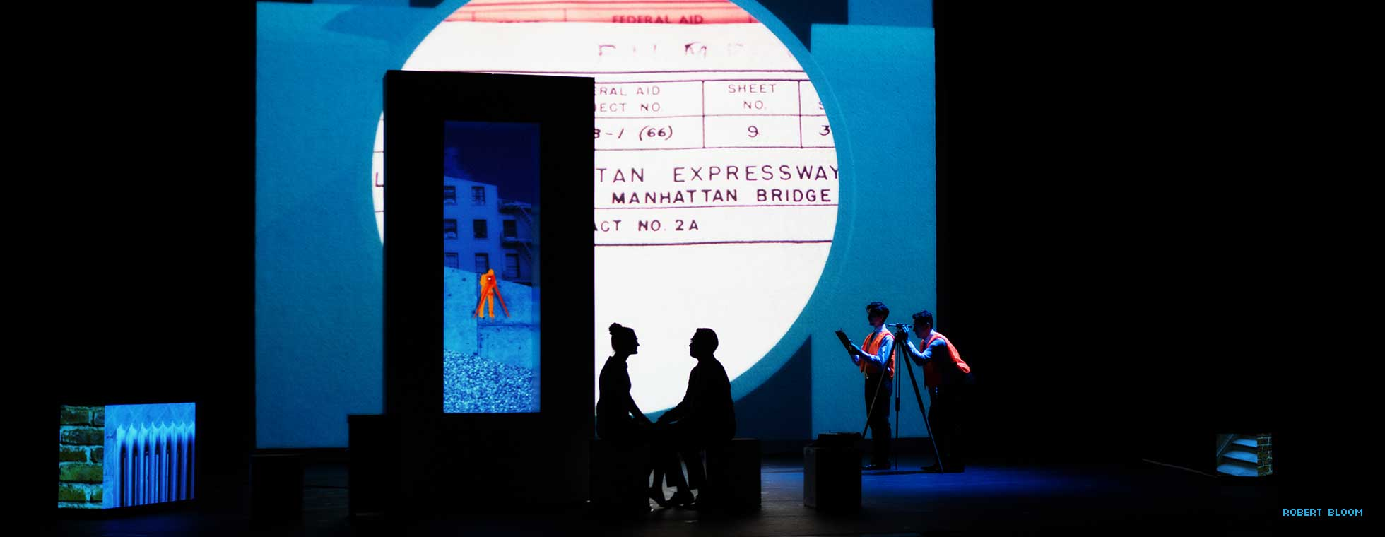 Two figures sit on stage surrounded by projected graphics and photos.