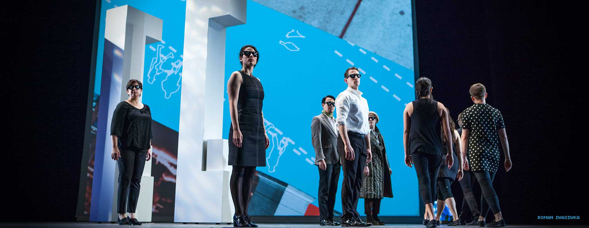 Actors stand on stage wearing sunglasses while surrounded by projections of graphs and maps.