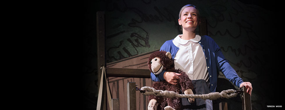 An actress clutching a stuffed monkey portrays a young Jane dressed in a schoolgirl skirt, blouse, and cardigan.