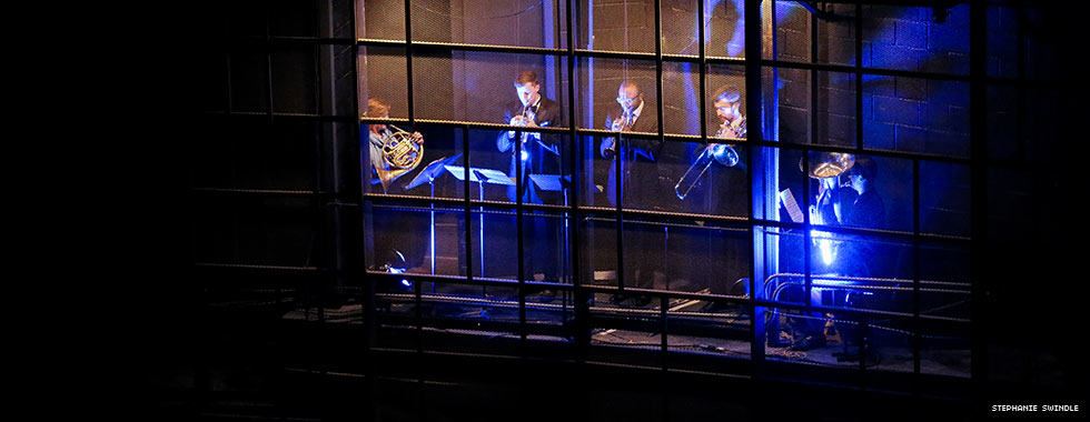 A light illuminates five brass musicians who perform in the mesh walls of Eisenhower Auditorium.