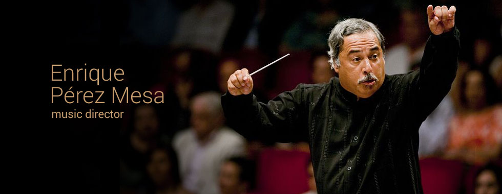Music director Enrique Pérez Mesa gestures to his orchestra with his raised hand and baton.