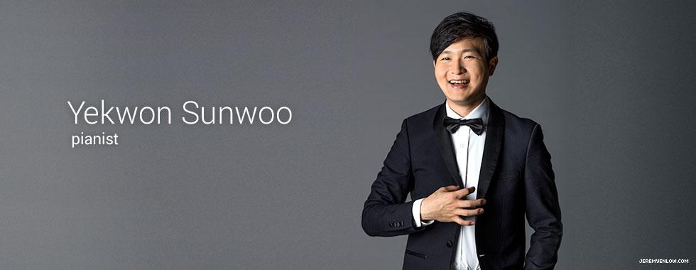Piano soloist Yekwon Sunwoo smiles at the camera wearing a tuxedo.