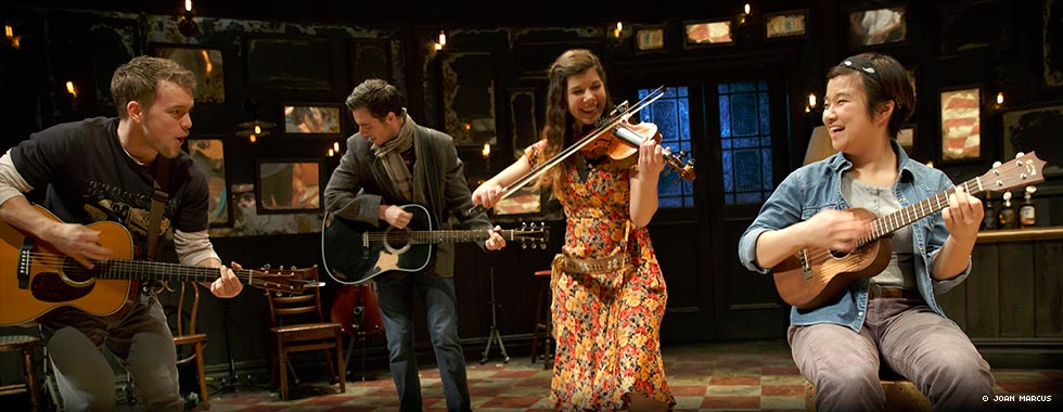 The musical's male and female protagonists—standing in the center and playing their guitar and violin, respectively—are flanked by a male guitarist to the left and a female guitarist to the right while they perform on stage in front of a set designed to look like the inside of a pub.