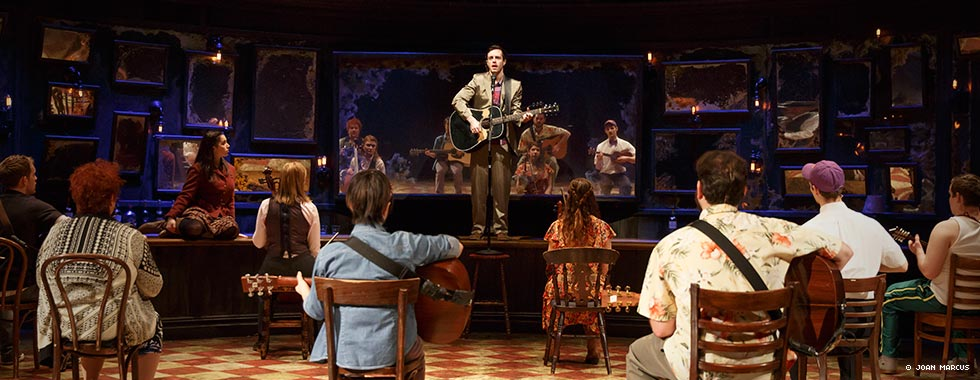 """""""Guy,"""" the main character in """"Once,"""" sings and plays guitar while standing on a short stage as members of the musical's cast sit facing him and help with the song's performance."""