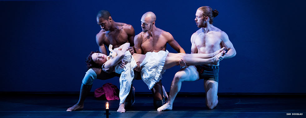"Three shirtless male dancers bent on one knee prop up a female dancer lying with eyes closed plank-style across their bent knees in Pilobolus' ""Shadowland."""