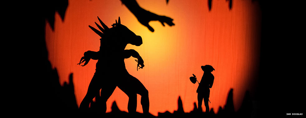"In Pilobolus' ""Shadowland,"" silhouetted dancers standing behind a screen depict an unidentified, horse-like animal while a dancer depicting a young girl carrying a hobo's sack on a stick shields herself from the creature."