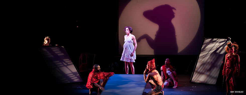 "Dancers in various states and styles of dress hold light screens while surrounding a dancer depicting a young girl coming of age in Pilobolus' ""Shadowland"" while behind her is displayed a silhouette of her image with an animal head."