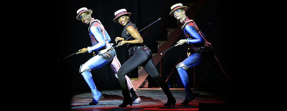 Three acrobats stand in unison with each of their right legs bent at the knee and left legs extended straight behind them while they each cradle a baton on their right arms.