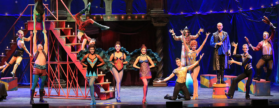 A diverse cast men and women with their arms and hands in various positions wear festive circus-themed leotards and stand in front of stage props.