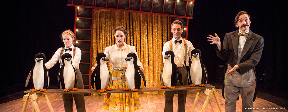 A man wearing a suit jacket gestures to three actors each standing in front of two stuffed penguins.