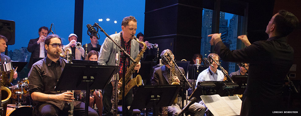 A saxophone musician stands in the center and performs while surrounded by musicians who sit at their music stands and play.