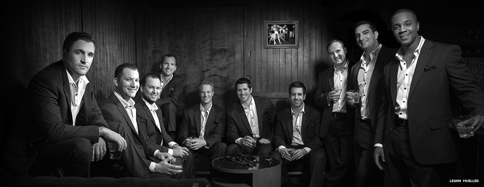 The ten vocalists of a cappella group Straight No Chaser hold drinks and smile for the camera.